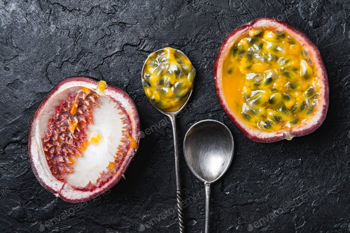 Slised passion fruit with silver spoons