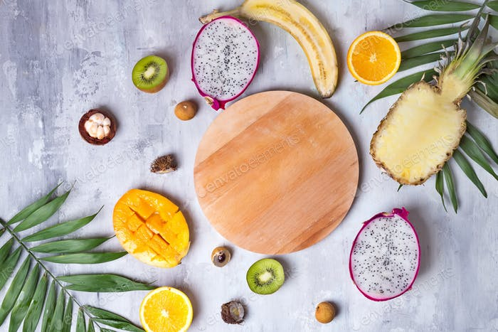 Tropical fruits assortment with wooden plate for copy space on a stone light background pattern. Top