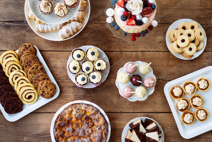 Table with cake, pie, cupcakes, cookies, tarts and cakepops