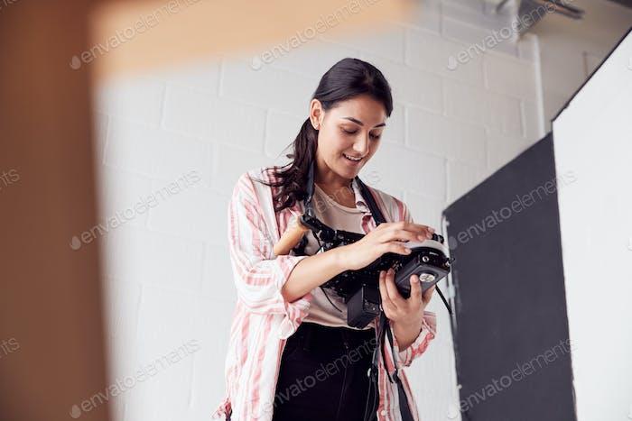 Female Crew Member On Video Film Set Operating Wireless Follow Focus Module In White Studio