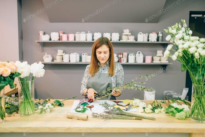 Female florist prepares flower composition