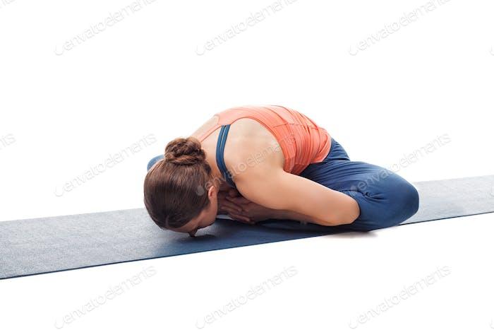 Woman practices yoga asana Baddha konasana