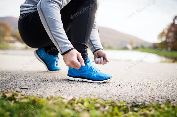Unrecognizable young runner tying shoelaces.