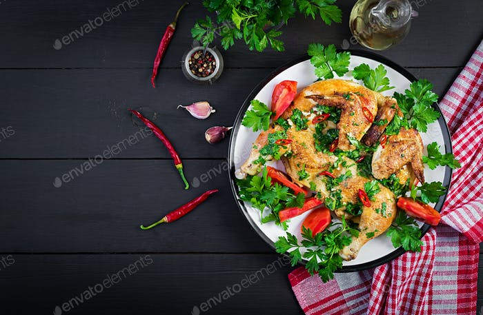 Grilled fried roast Chicken Tabaka in plate on wooden background.