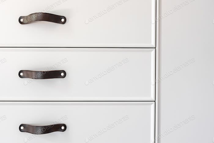 Black handles of the kitchen drawer or cabinet.