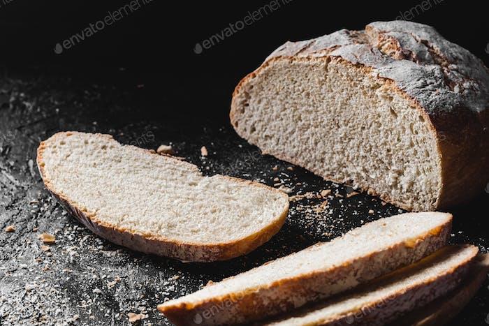 Geschnittener Laib dunkles hausgemachtes Brot mit Mehl bestäubt