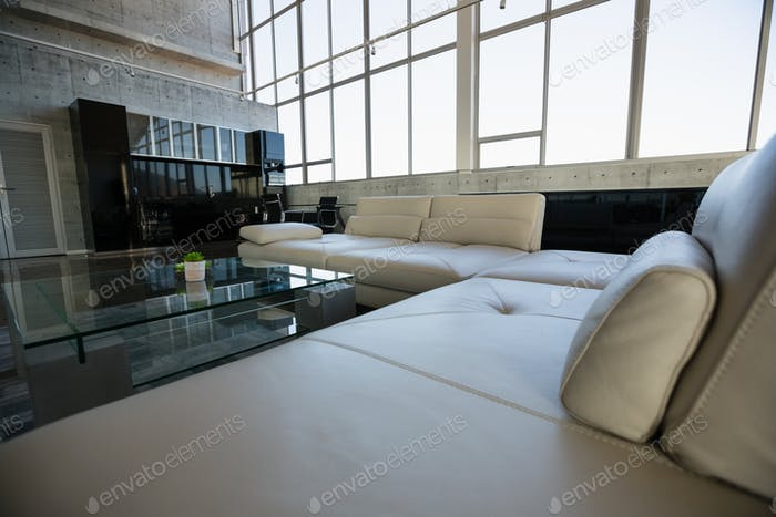 Glass table by empty white sofa at office