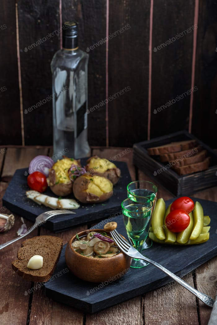 Vodka with pickled mushrooms on the Board. On wooden background.