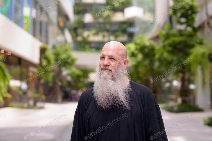 Face of happy mature handsome bald bearded man thinking with nature in the city