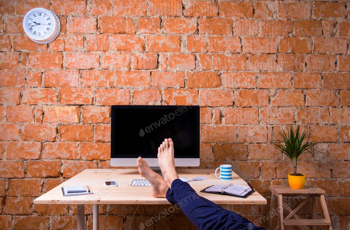 Feet Of Businessman Sitting At Office Desk Brick Wall