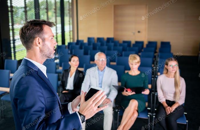 Referent hält einen Vortrag über Unternehmens- Business Conference für das Publikum im Konferenzsaal