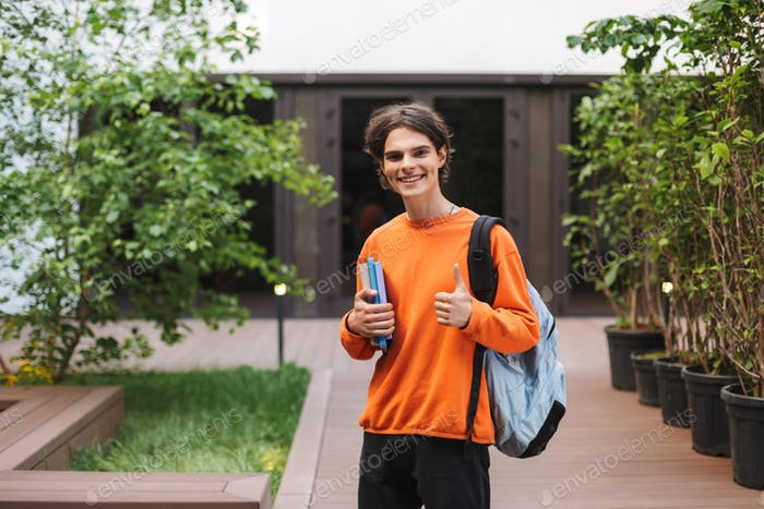 Joyful man standing with backpack and books in hand and happily showing big thumb up