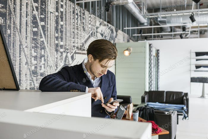Salesman using mobile phone in factory