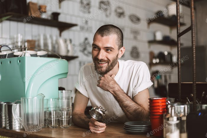 Smiling barista at bar counter happily looking aside holding portafilter in hand in cafe