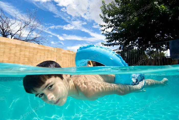 Boy swimming in pool with float ring
