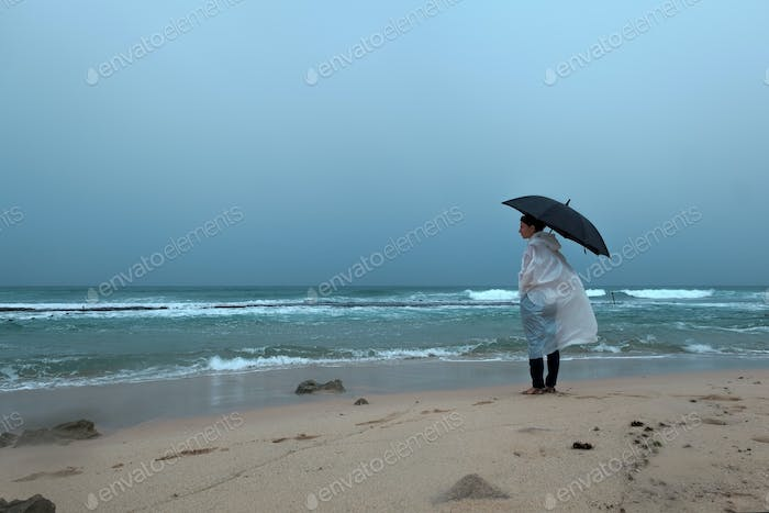 Young woman walking with an umbrella in front of ocean in rainy weather