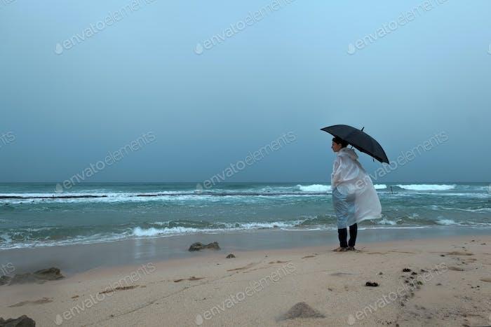 Junge Frau zu Fuß mit einem Regenschirm vor dem Meer bei Regenwetter