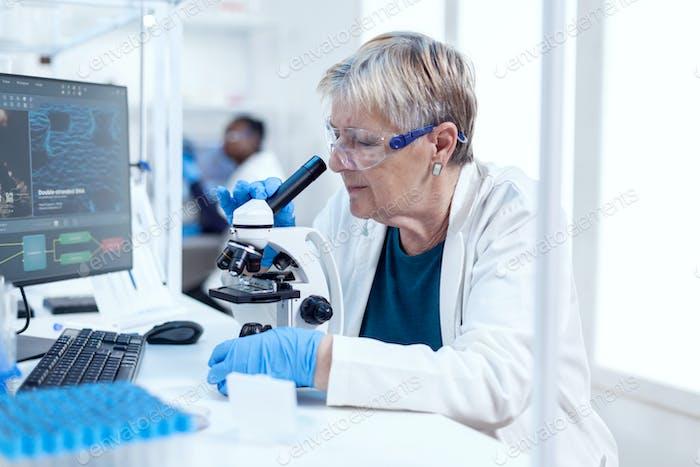 Senior scientist conducting scientific experiment
