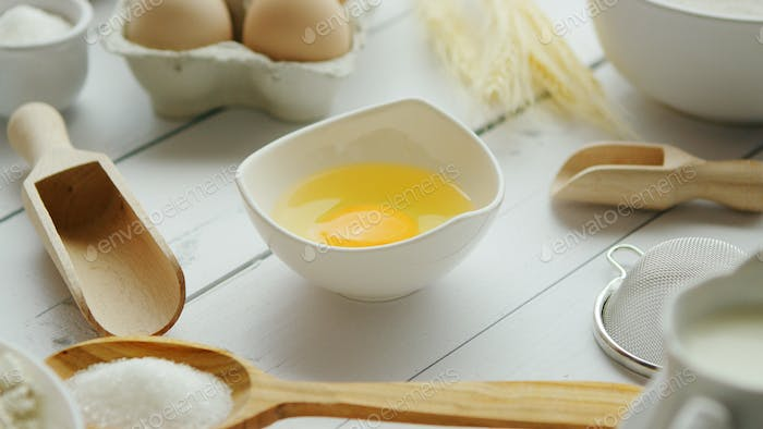 Utensils and ingredient around bowl with yolk