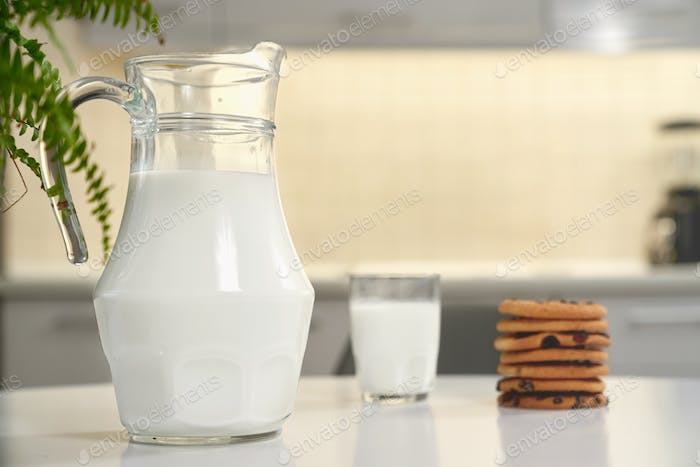 Pitcher and glass of milk, tasty american cookies