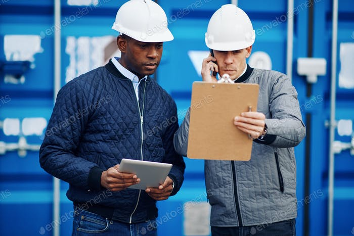 Two engineers checking inventory in a shipping yard