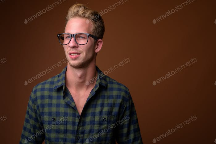 Studio shot of young handsome man against brown background