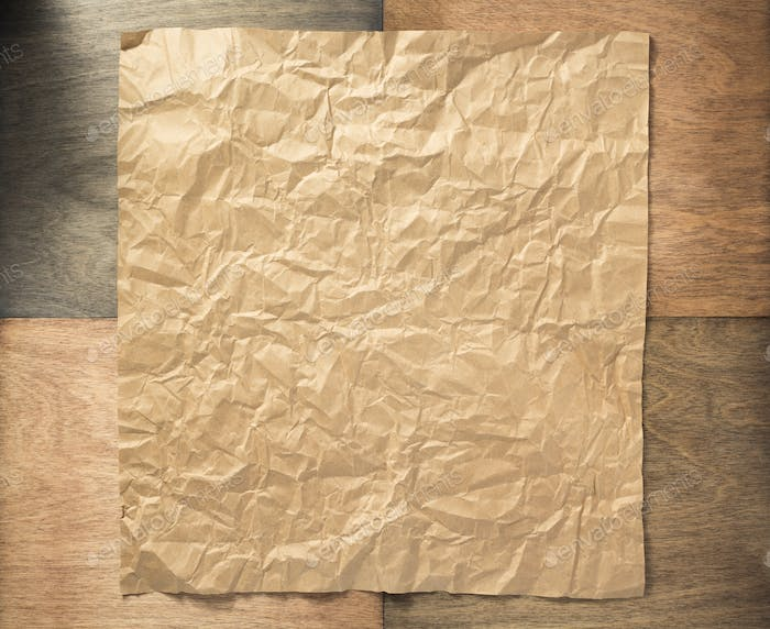 wrinkled paper at wooden background