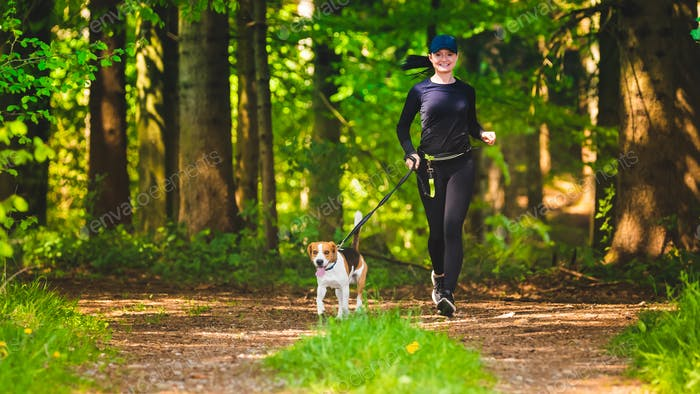 Sport girl is running with a dog (Beagle) at the spring sunny day on the forest path.
