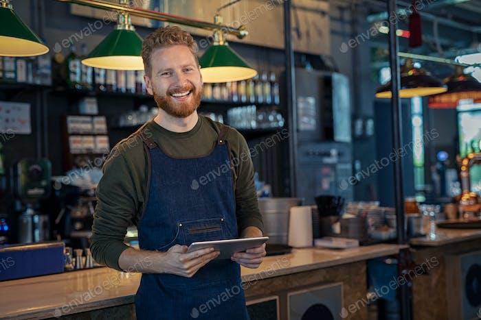 Smiling Waiter ready to take order at pub
