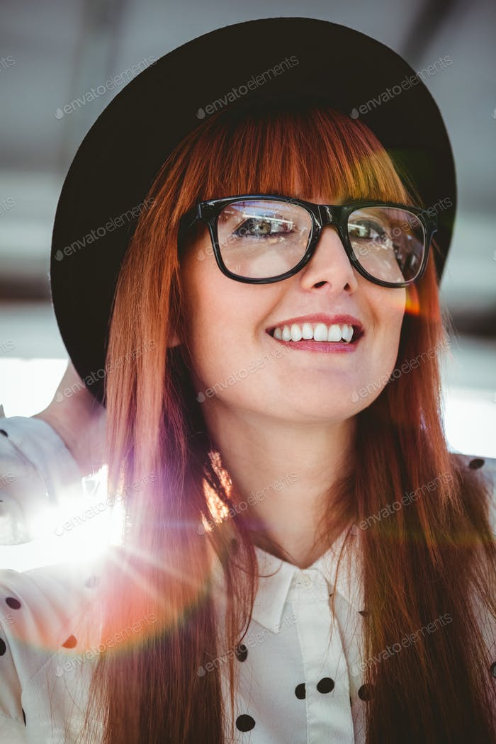 Attractive smiling hipster woman with hat in a bright room