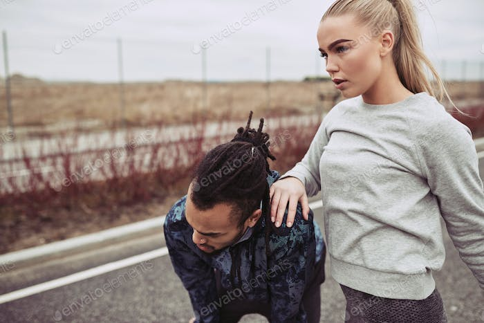 Young couple catching their breath while out for a run