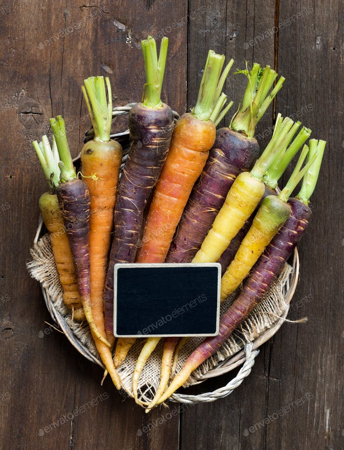 Fresh organic rainbow carrots and a small chalkboard on wood