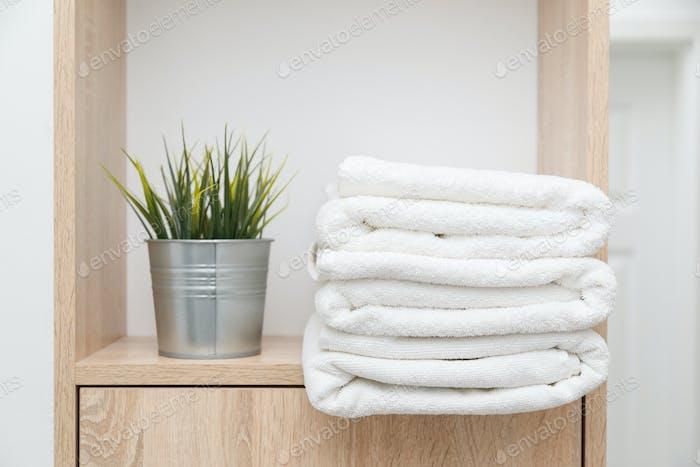 Stapel saubere Handtücher auf dem Regal mit Grüns im Eimer
