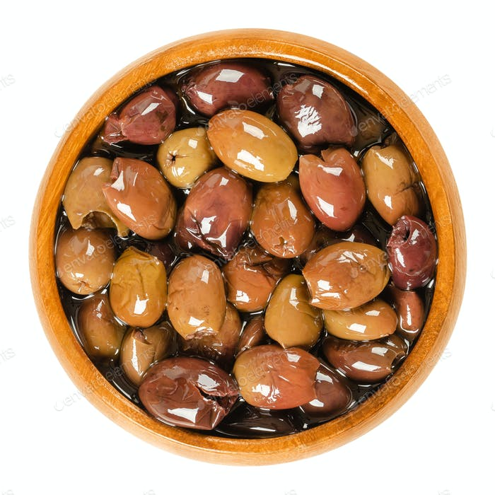 Pitted Taggiasca olives in wooden bowl over white