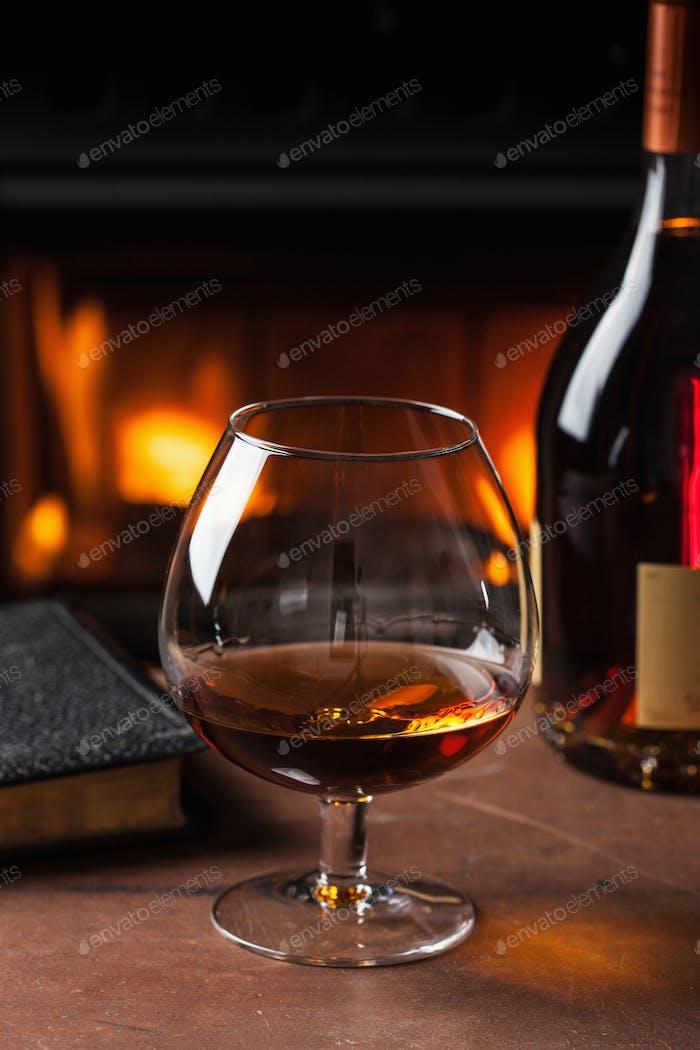 Glas Cognac vor dem Kamin