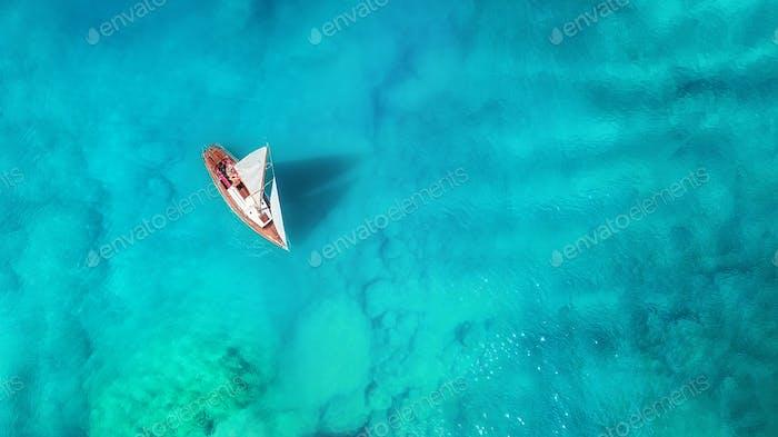 Blick auf die Yacht und das türkisfarbene Meer. Sommer-Meereslandschaft von der Drohne