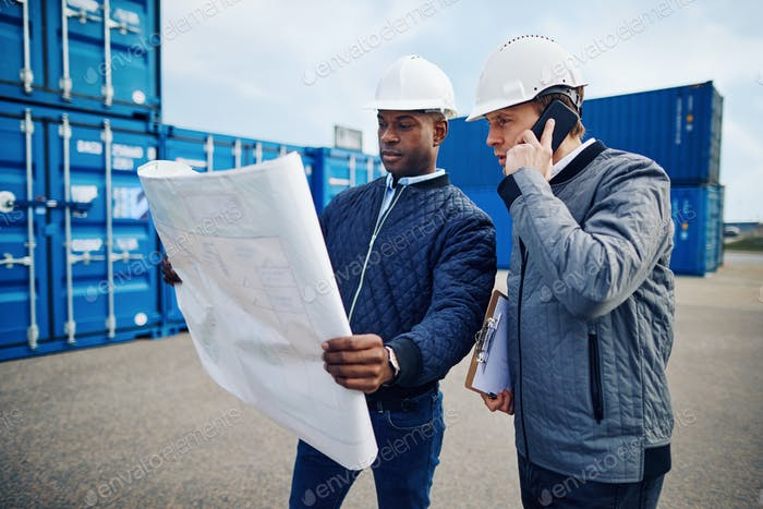 Engineers reading building plans while standing in a freight yard