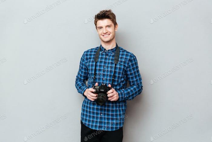 Lächelnder Mann hält Kamera in den Händen