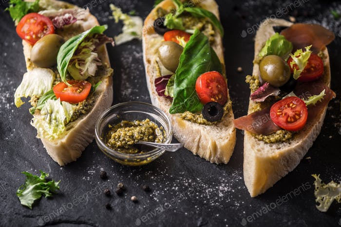 Ciabatta with olives , tomatoes and basil on the black stone table