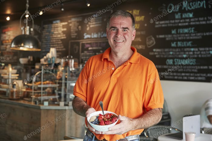 Mature Man Holding Healthy Breakfast In Coffee Shop