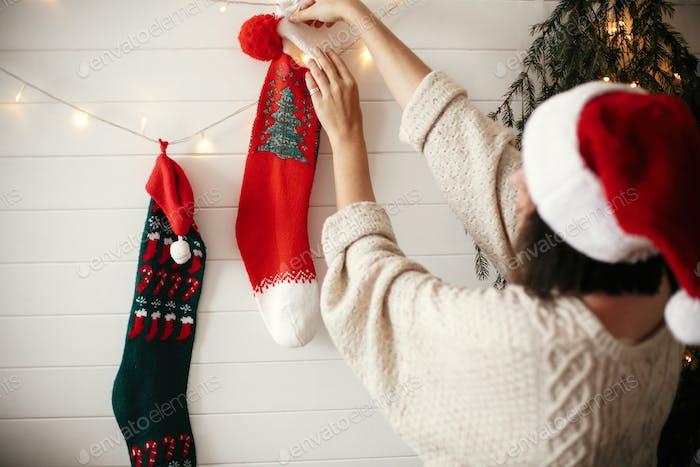 Stilvolles Mädchen in gemütlichen Pullover und Weihnachtsmann Hut Dekoration Raum für Weihnachten Urlaub
