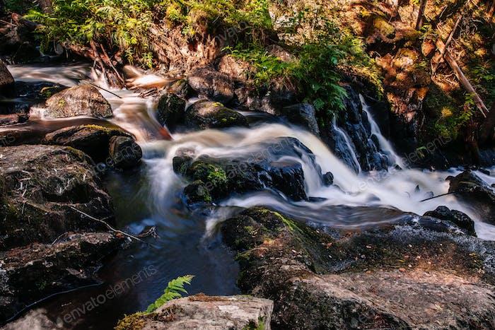 Schneller Fluss fließendes Wasser des Wasserfalls in Finnland