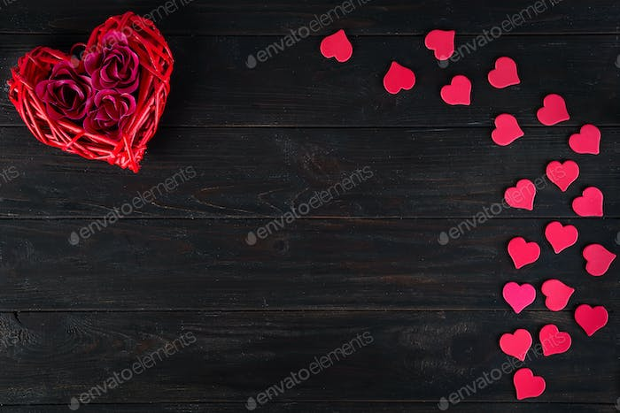 Wooden rustic red decorative heart hanging and roses on dark wooden background with space, flat lay