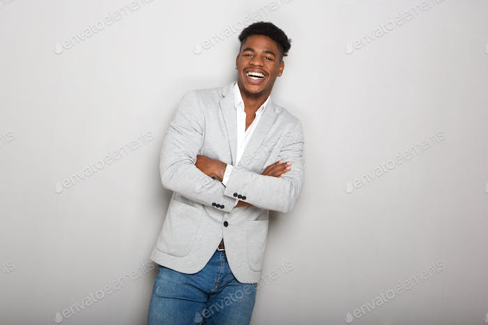 happy young african american businessman laughing with arms crossed against gray background