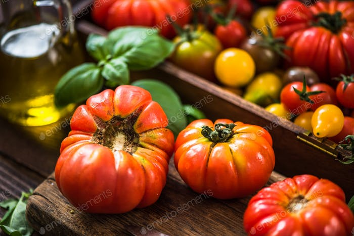 Colorful variety of fresh tomatoes on wooden serving board