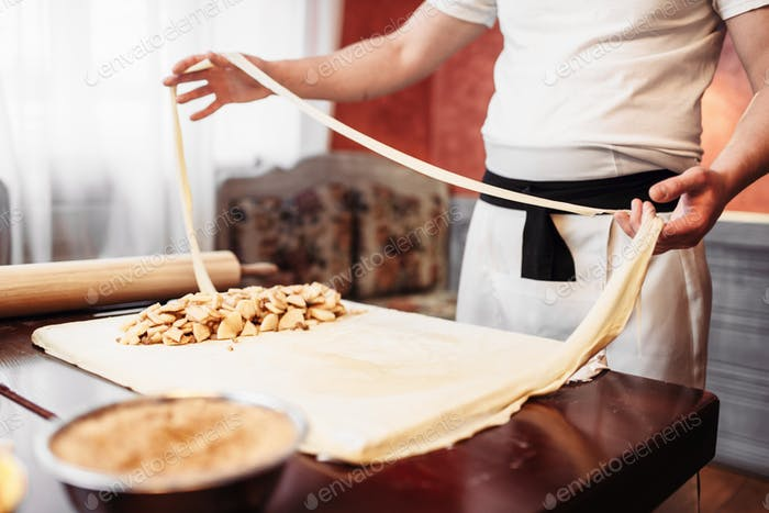 Male chef prepares dough for apple strudel