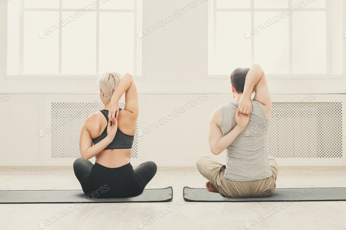 Young couple in yoga class, back stretching