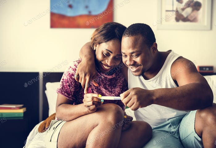 Black couple looking at pregnancy test