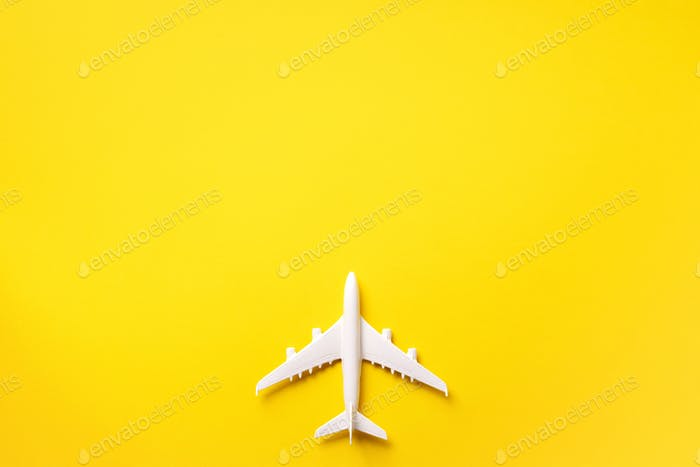 Travel, vacation concept. White model airplane on yellow color background with copy space. Top view