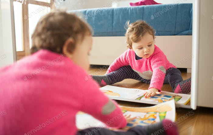 Toddler baby girl playing with fairy tales book